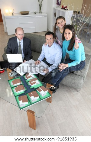 Family with estate agent - stock photo