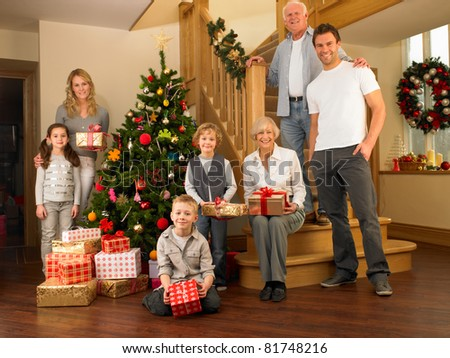 Family with gifts around the Christmas tree - stock photo