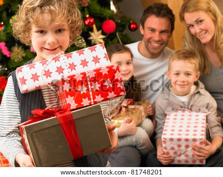 Family with gifts in front of Christmas tree