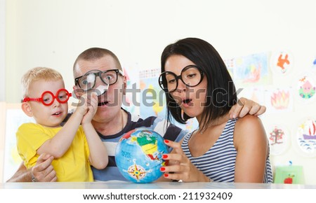 Family with glasses studying a globe with magnifier - stock photo