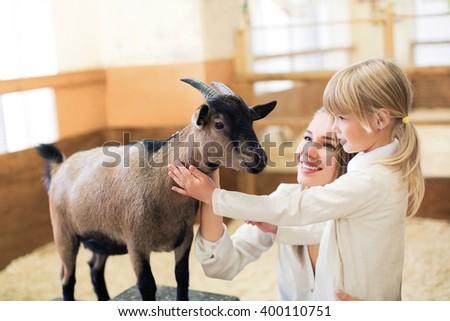 Family with goat  on farm - stock photo