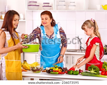 Family with grandmother and child cooking at kitchen. - stock photo
