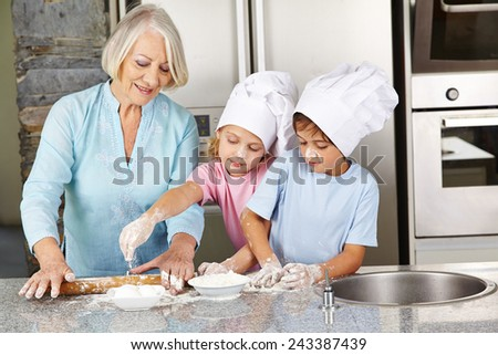 Family with grandmother and children baking christmas cookies in kitchen - stock photo