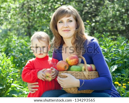 family with  harvested apples in garden - stock photo