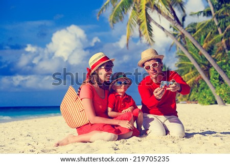 family with kid making self photo on the beach using phone - stock photo