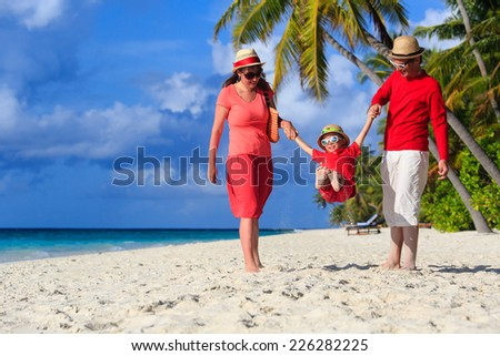 family with kid playing on tropical sand beach - stock photo