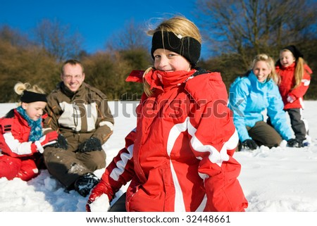 Family with kids having a snowball fight in winter on top of a hill in the snow - stock photo