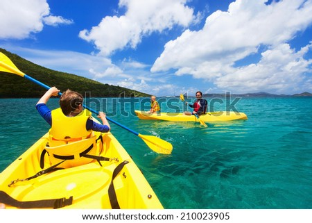 Family with kids paddling on colorful yellow kayaks at tropical ocean water during summer vacation - stock photo