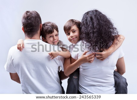 Family with kids - parents holding their sons - stock photo