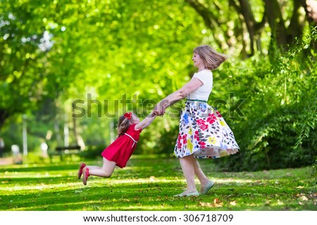 Family with kids playing in a park. Woman and little girl spin and dance in the garden. Grandmother and granddaughter play outdoors. Summer dress for mother and daughter. Active parents with children. - stock photo