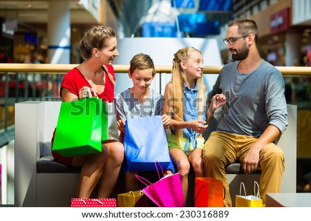 Family with kids shopping in mall having a break - stock photo