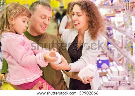 family with little girl buy milk in supermarket - stock photo