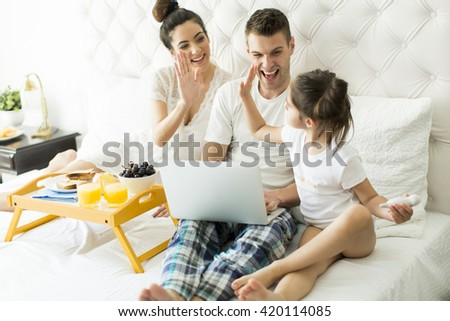 Family with little girl having breakfest in the bed. - stock photo