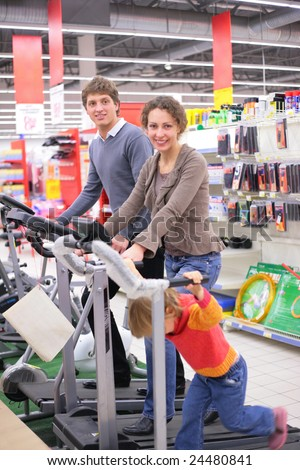 Family with little girl on sports training apparatus in shop - stock photo