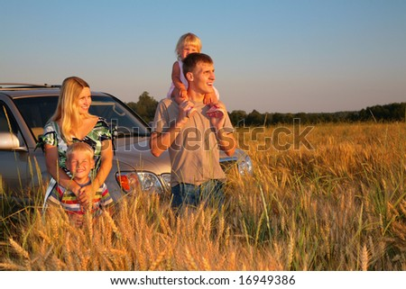 Family with offroad car on wheaten field - stock photo