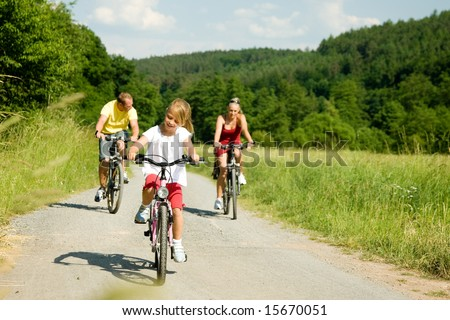 Family with one child riding their bicycles on a summer day (focus on the girl in front) - stock photo
