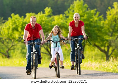 Family with one girl having a weekend excursion on their bikes or bicycles on a summer day in beautiful landscape - stock photo