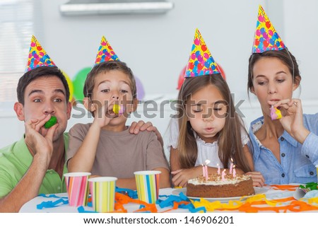 Family with party horn celebrating their daughter party who is blowing her candles