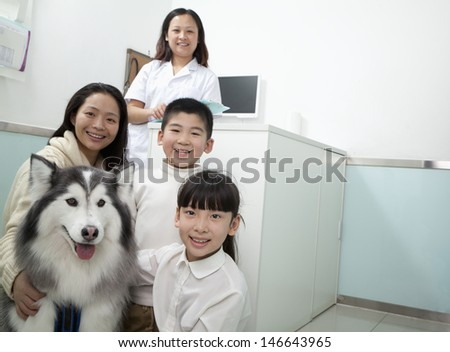 Family with pet dog in veterinarian's office - stock photo