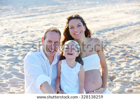 Family with pregnant mother on the beach sand happy in summer vacations - stock photo