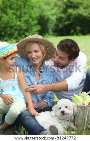 Family with small white dog and basket of vegetables - stock photo