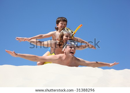 family with son lying on sand with hands up