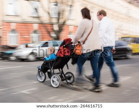 Family with stroller on zebra crossing in motion blur - stock photo