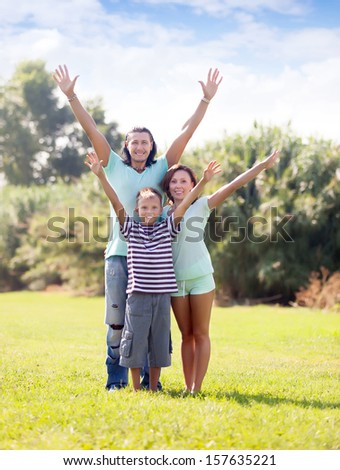 family  with teenage boy enjoying time in summer park