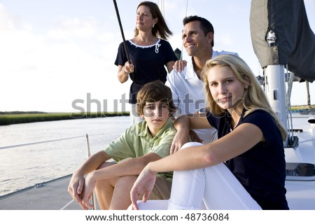 Family with teenage children sitting on boat at dock on sunny day - stock photo