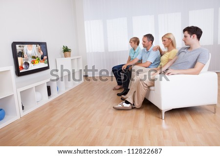 Family with teenage children sitting together on a sofa in the living room watching widescreen television