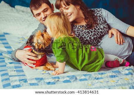 Family with their dog lie on the bed - stock photo