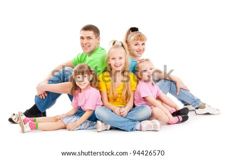 Family with three daughters sit on a floor, a white background - stock photo