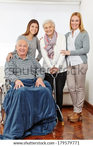 Family with three generations and senior couple at home - stock photo