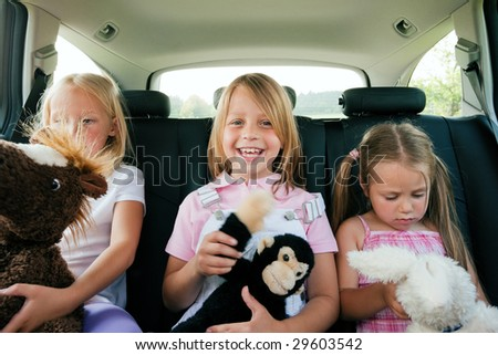Family with three kids in a car, kids sitting on the backseats - stock photo