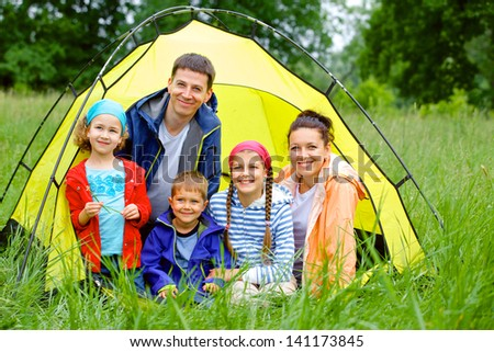 Family with three kids in tent in camping on the nature. - stock photo