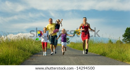 Family with three kids running down a hill - stock photo