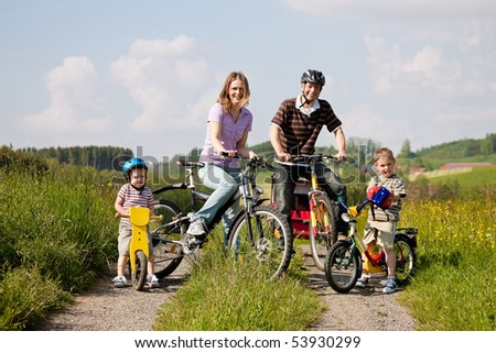 Family with two children having a weekend excursion on their bikes on a summer day in beautiful landscape, for safety and protection they are wearing helmets - stock photo
