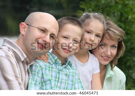 family with two children in early fall park near pond. focus on little boy's face. - stock photo