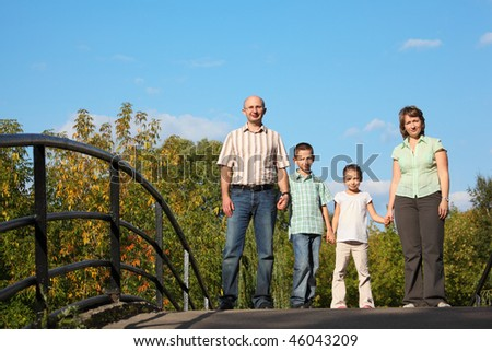 family with two children is standing on bridge and looking at camera. - stock photo
