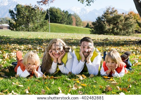 Family with two children lying lawn with green grass and yellow leaves