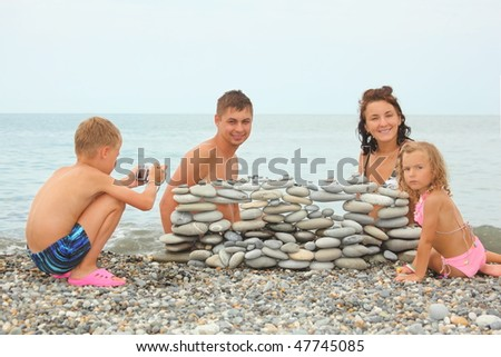 family with two children near construction of pebbles. little boy with photo camera.