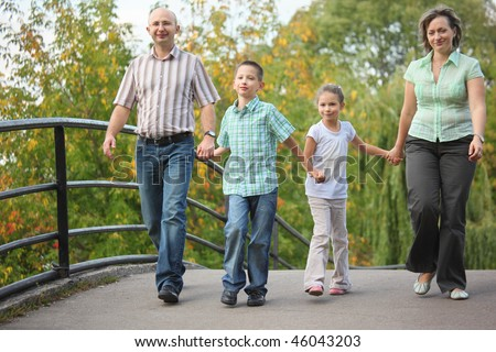 family with two children walking on bridge in early fall park. family is handies. focus on little boy - stock photo