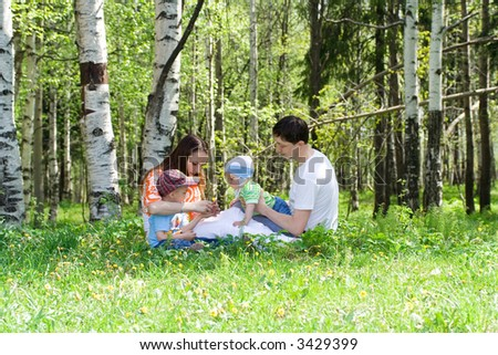 Family with two kids at meadow. Summer. Grass - stock photo
