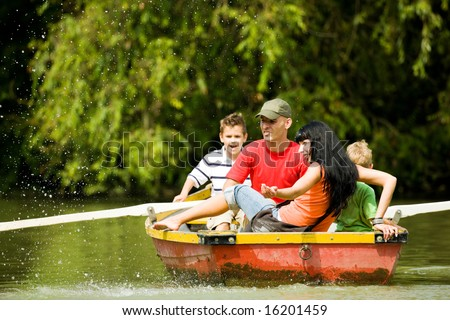 Family with two kids having a boat trip, a lot of water drops in the air (focus on the mother, shallow depth of field) - stock photo