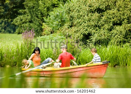 Family with two kids having a boat trip on a lake, in the background lots of trees and flowers - stock photo
