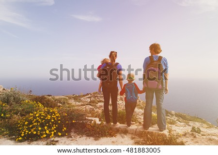 family with two kids hiking in scenic mountains