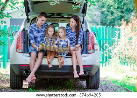Family with two kids looking at map while traveling by car - stock photo