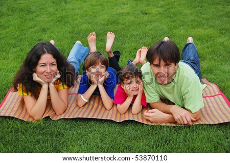 Family with two kids on the grass - stock photo