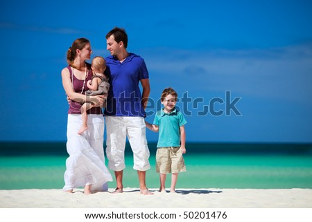Family with two kids on white sand tropical beach - stock photo