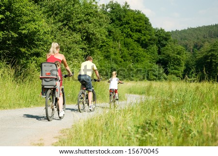 Family with two kids riding their bicycles on a summer day (seen from behind) - stock photo